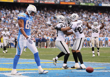 SAN DIEGO - DECEMBER 05:  (L-R) Wide receiver Malcolm Floyd #80 of the San Diego Chargers looks down, as Stevie Brown #27 and Nnamdi Asomugha #21 the Oakland Raiders celebrate a broken play in the third quarter at Qualcomm Stadium on December 5, 2010 in S