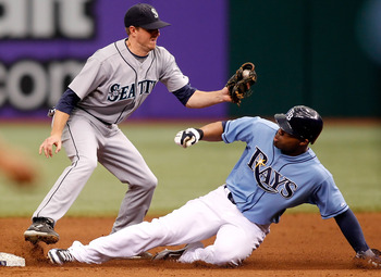 ST. PETERSBURG - MAY 16:  Outfielder Carl Crawford #13 of the Tampa Bay Rays steals second base as shortstop Josh Wilson #16 of the Seattle Mariners takes the throw during the game at Tropicana Field on May 16, 2010 in St. Petersburg, Florida.  (Photo by