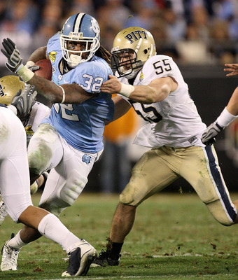 CHARLOTTE, NC - DECEMBER 26:  Max Gruder #55 of the Pittsburgh Panthers tackles Ryan Houston #32 of the North Carolina Tar Heels during their game on December 26, 2009 in Charlotte, North Carolina.  (Photo by Streeter Lecka/Getty Images)