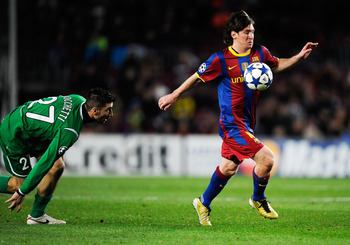 BARCELONA, SPAIN - DECEMBER 07:  Salvatore Bocchetti of Rubin Kazan looks to Lionel Messi of Barcelona as he controls the ball during the Csampions League match between Barcelona and Rubin Kazan at Camp Nou Stadiumon December 7, 2010 in Barcelona, Spain.