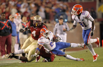 TALLAHASSEE, FL - NOVEMBER 27:  Jeff Demps #2 of the Florida Gators is tackled by Terrance Parks #4 of the Florida State Seminoles  during a game at Doak Campbell Stadium on November 27, 2010 in Tallahassee, Florida.  (Photo by Mike Ehrmann/Getty Images)