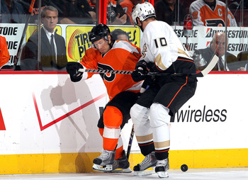 PHILADELPHIA - OCTOBER 21:  Kimmo Timonen #44 of the Philadelphia Flyers plays the puck against Corey Perry #10 of the Anaheim Ducks on October 21, 2010 at Wells Fargo Center in Philadelphia, Pennsylvania. Anaheim defeated the Flyers 3-2.  (Photo by Jim M