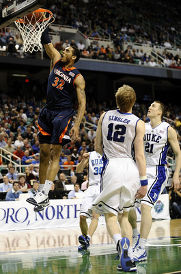 GREENSBORO, NC - MARCH 12:  Mike Scott #32 of the University of Virginia Cavaliers drives by Miles Plumlee #21 and Kyle Singler #12  of the Duke Blue Devils guards in their quarterfinal game in the 2010 ACC Men's Basketball Tournament at the Greensboro Co