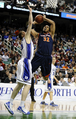 GREENSBORO, NC - MARCH 12:  MIles Plumlee #21 of the Duke Blue Devils guards Mike Scott #32  of the University of Virginia Cavaliers in their quarterfinal game in the 2010 ACC Men's Basketball Tournament at the Greensboro Coliseum on March 12, 2010 in Gre