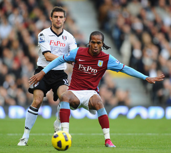 LONDON, ENGLAND - NOVEMBER 06:  Nathan Delfouneso of Aston Villa is challenged by Aaron Hughes of Fulham during the Barclays Premier League match between Fulham and Aston Villa at Craven Cottage on November 6, 2010 in London, England.  (Photo by Mike Hewi