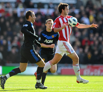 STOKE ON TRENT, ENGLAND - OCTOBER 24:  Marc Wilson of Stoke controls the ball ahead of Dimitar Berbatov of Manchester United  during the Barclays Premier League match between Stoke City and Manchester United at Britannia Stadium on October 24, 2010 in Sto