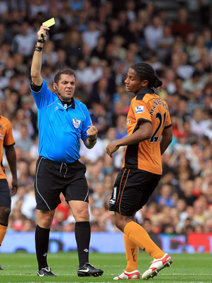 LONDON, ENGLAND - SEPTEMBER 11:  Phil Dowd the referee gives Michael Mancienne of Wolves a yellow card during the Barclays Premier League match between Fulham and Wolverhampton Wanderers at Craven Cottage on September 11, 2010 in London, England.  (Photo