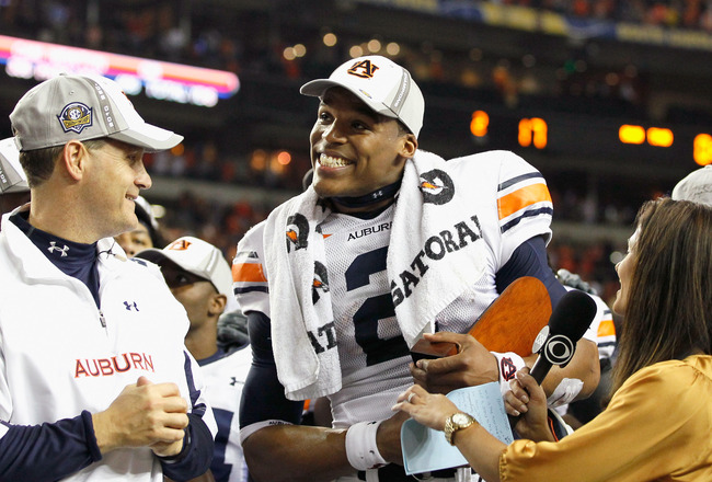 ATLANTA, GA - DECEMBER 04:  CBS sideline reporter Tracy Wolfson (R) and head coach Gene Chizik look on as quarterback Cam Newton #2 of the Auburn Tigers accepts the MVP trophy after their 56-17 win over the South Carolina Gamecocks during the 2010 SEC Cha
