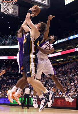 PHOENIX - OCTOBER 12:  Kyrylo Fesenko #44 of the Utah Jazz puts up a shot past Josh Childress #1 of the Phoenix Suns during the preseason NBA game at US Airways Center on October 12, 2010 in Phoenix, Arizona. NOTE TO USER: User expressly acknowledges and