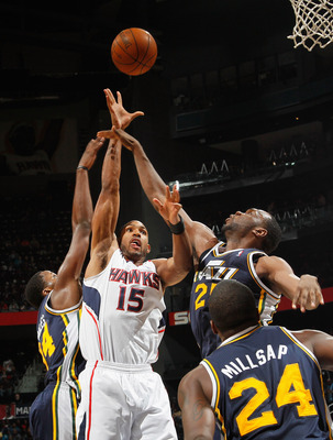 ATLANTA - NOVEMBER 12:  Al Horford #15 of the Atlanta Hawks shoots against C.J. Miles #34, Al Jefferson #25 and Paul Millsap #24 of the Utah Jazz at Philips Arena on November 12, 2010 in Atlanta, Georgia.  NOTE TO USER: User expressly acknowledges and agr
