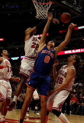 CHICAGO - NOVEMBER 04: Danilo Gallinari #8 of the New York Knicks is fouled while shooting by Taj Gibson #22 of the Chicago Bulls as Kyle Korver #26 defends at the United Center on November 4, 2010 in Chicago, Illinois. NOTE TO USER: User expressly acknow