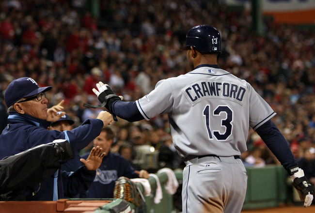BOSTON - OCTOBER 14:  Manager Joe Maddon of the Tampa Bay Rays congratulates Carl Crawford #13 after scoring during game four of the American League Championship Series against the Boston Red Sox during the 2008 MLB playoffs at Fenway Park on October 14,