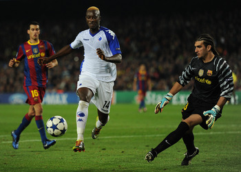 BARCELONA, SPAIN - OCTOBER 20:  Dame N'Doye (L) of FC Copenhagen tries to score past goalkeeper Jose Pinto of Barcelona during the UEFA Champions League group D match between Barcelona and FC Copenhagen at the Camp Nou stadium on October 20, 2010 in Barce