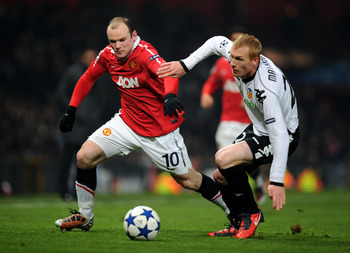 MANCHESTER, ENGLAND - DECEMBER 07:  Jeremy Mathieu of Valencia challenges Wayne Rooney of Manchester United during the UEFA Champions League Group C match between Manchester United and Valencia at Old Trafford on December 7, 2010 in Manchester, England.