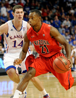 LAS VEGAS - NOVEMBER 27:  Kyle Fogg #21 of the Arizona Wildcats drives against Tyrel Reed #14 of the Kansas Jayhawks during the championship game of the Las Vegas Invitational at The Orleans Arena November 27, 2010 in Las Vegas, Nevada. Kansas won 87-79.