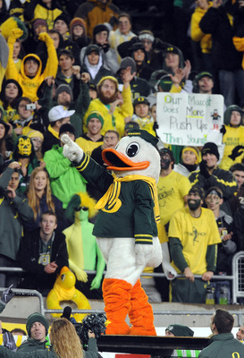 EUGENE, OR - NOVEMBER 26: Oregon Ducks fans cheer as mascot 'Puddles' prepares to do some push ups in the fourth quarter of the game against the Arizona Wildcats at Autzen Stadium on November 26, 2010 in Eugene, Oregon. Puddles does push ups for every poi