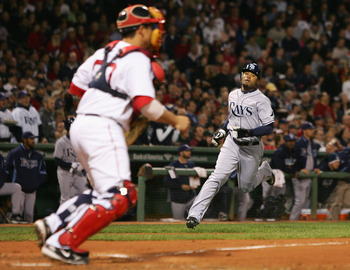 BOSTON - OCTOBER 14:  Carl Crawford #13 of the Tampa Bay Rays comes in to score a run against the Boston Red Sox in the fifth inning of game four of the American League Championship Series during the 2008 MLB playoffs at Fenway Park on October 14, 2008 in