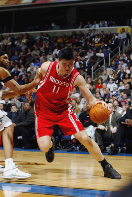 WASHINGTON - JANUARY 13:  Yao Ming #11 of the Houston Rockets drives around Etan Thomas #36 of the Washington Wizards during the game at MCI Center on January 13, 2004 in Washington, DC.  The Rockets won 93-80.  NOTE TO USER: User expressly acknowledges a