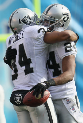 SAN DIEGO - DECEMBER 05:  Safety Michael Huff (R) #24 the Oakland Raiders is congratulated by teammate Mike Mitchell #34 after intercepting a pass against the San Diego Chargers during the first quarter at Qualcomm Stadium on December 5, 2010 in San Diego