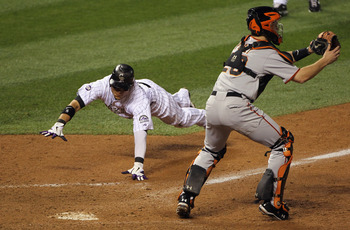 DENVER - SEPTEMBER 25:  Carlos Gonzalez #5 of the Colorado Rockies dives home to score the game winning run behind catcher Buster Posey #28 of the San Francisco Giants on a double by Troy Tulowitzki off of relief pitcher Brian Wilson of the Giants in the