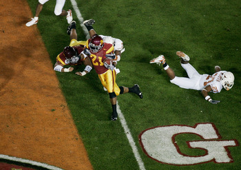 PASADENA, CA - JANUARY 04:  Running back LenDale White #21 of the USC Trojans scores on a 4-yard run against Michael Griffin #27 of the Texas Longhorns in the first quarter during the BCS National Championship Rose Bowl Game on January 4, 2006 in Pasadena
