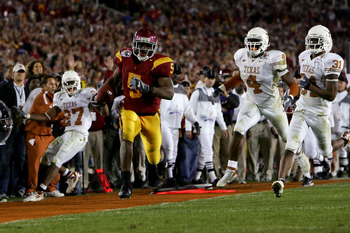 PASADENA, CA - JANUARY 04:  Reggie Bush #5 of the USC Trojans runs past Michael Griffin #27, Drew Kelson #4 and Aaron Ross #31 of the Texas Longhorns en route to scoring a 26 yeard touchdown in the fourth quarter of the BCS National Championship Rose Bowl