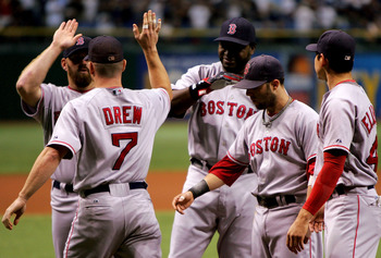 TAMPA, FL - OCTOBER 10:  J.D. Drew #7 of the Boston Red Sox high fives teammate Kevin Youkilis #20  in front of David Ortiz #34, Dustin Pedroia #15 and Jacoby Ellsbury #46 before they take on the Tampa Bay Devil Rays in game one of the American League Cha
