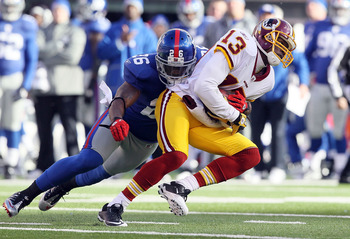 EAST RUTHERFORD, NJ - DECEMBER 05: Anthony Armstrong #13 of the Washington Redskins is tackled by Antrel Rolle #26 of the New York Giants on December 5, 2010 at the New Meadowlands Stadium in East Rutherford, New Jersey.  (Photo by Jim McIsaac/Getty Image