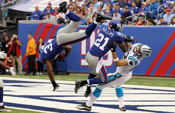 EAST RUTHERFORD, NJ - SEPTEMBER 12:  Deon Grant #34 of the New York Giants intercepts a pass in the endzone intended for Gary Barnidge #82 of the Carolina Panthers as teammate Kenny Phillips #21 defends during the first quarter on September 12, 2010 at th