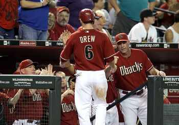 PHOENIX - AUGUST 18:  Manager Kirk Gibson of the Arizona Diamondbacks greets Stephen Drew #6 after he scored against the Cincinnati Reds during the Major League Baseball game at Chase Field on August 18, 2010 in Phoenix, Arizona. The Reds defeated the Dia
