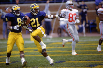 1991:  Desmond Howard #21 of the Michigan Wolverines runs makes the 'Heisman' pose right after making a 93 yard touchdown against Ohio State circa 1991 in Ann Arbor, Michigan.  Wolverines won 31 -3. (Photo by Getty Images)