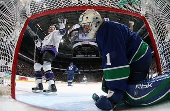 VANCOUVER, CANADA - APRIL 3:  Roberto Luongo #1 of the Vancouver Canucks sits dejected in the crease as Jaroslav Modry #44 of the Los Angeles Kings celebrates a Los Angeles goal during their NHL game at General Motors Place on April 3, 2007 in Vancouver,