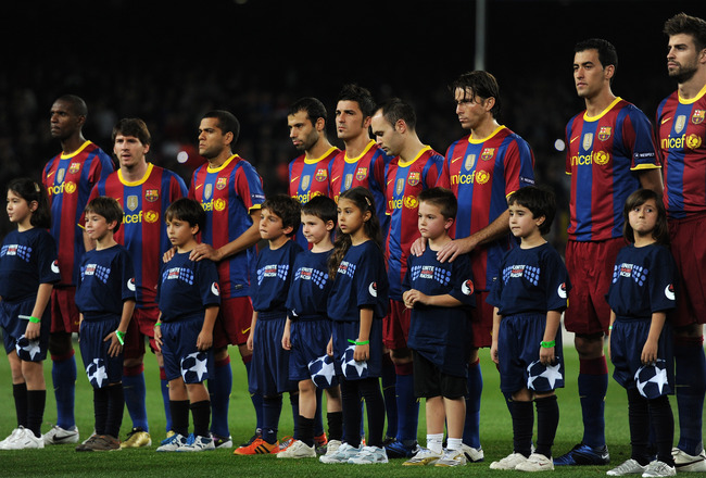 BARCELONA, SPAIN - OCTOBER 20:  Mascots wearing Unite Against Racism shirts pose with Barcelona players prior to the start of the UEFA Champions League group D match between Barcelona and FC Copenhagen at the Camp Nou stadium on October 20, 2010 in Barcel