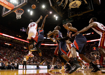 MIAMI, FL - DECEMBER 04:  Josh Smith #5 of the Atlanta Hawks drives to the basket against Joel Anthony #50 of  the Miami Heat during a game at American Airlines Arena on December 4, 2010 in Miami, Florida. NOTE TO USER: User expressly acknowledges and agr