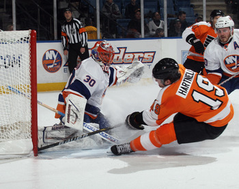 UNIONDALE, NY - DECEMBER 05: Scott Hartnell #19 of the Philadelphia Flyers is tripped up as he attempts to reach a puck against Dwayne Roloson #30 of the New York Islanders at the Nassau Coliseum on December 5, 2010 in Uniondale, New York.  (Photo by Bruc
