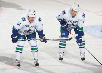 BUFFALO, NY - NOVEMBER 15: Raffi Torres #13 and Christian Ehrhoff #5 of the Vancouver Canucks wait for  a faceoff against the Buffalo Sabres  at HSBC Arena on November 15, 2010 in Buffalo, New York. Buffalo won 4-3 in overtime.  (Photo by Rick Stewart/Get