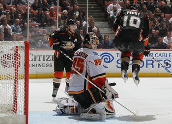 ANAHEIM, CA - DECEMBER 10:  (L-R) Corey Perry #10 of the Anaheim Ducks jumps to deflect the puck as goaltender Henrik Karlsson #35 of the Calgary Flames defends his net  in the third period at the Honda Center on December 10, 2010 in Anaheim, California.