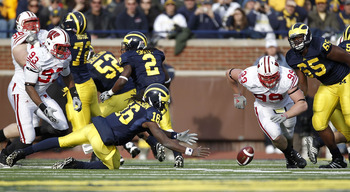 ANN ARBOR, MI - NOVEMBER 20:  Denard Robinson #16 of the Michigan Wolverines tries to beat J.J. Watt #99 of the Wisconsin Badgers to a fumble at Michigan Stadium on November 20, 2010 in Ann Arbor, Michigan. Wisconsin won the game 48-38.  (Photo by Gregory