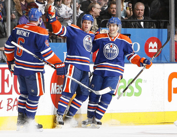 TORONTO, CANADA - DECEMBER 2: Ryan Whitney #6, Taylor Hall #4 and Jordan Eberle #14 of the Edmonton Oilers celebrate goal during game action against the New Jersey Devils at the Air Canada Centre December 2, 2010 in Toronto, Ontario, Canada. (Photo by Abe