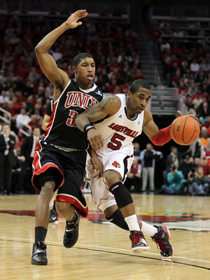 LOUISVILLE, KY - DECEMBER 11:  Chris Smith#5 of the Louisville Cardinals dribbles the ball while defended by Justin Hawkins #31 of the UNLV Runnin' Rebels during the game at KFC YUM! Center on December 11, 2010 in Louisville, Kentucky.  (Photo by Andy Lyo