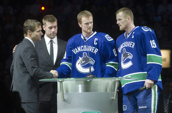 VANCOUVER, CANADA - DECEMBER 11: Henrik Sedin #33 and Daniel Sedin #22 of the Vancouver Canucks along with Mattias Ohlund #5 of the Tampa Bay Lightning greet former Canuck Markus Naslund during a pre-game ceremony to retire Naslund's jersey prior to NHL a