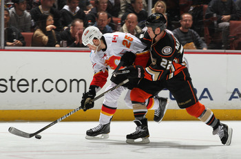 ANAHEIM, CA - DECEMBER 10:  Todd Marchant #22 of the Anaheim Ducks and David Moss #25 of the Calgary Flames battle for the puck in the third period at the Honda Center on December 10, 2010 in Anaheim, California. The Ducks defeated the Flames 3-2 in a sho