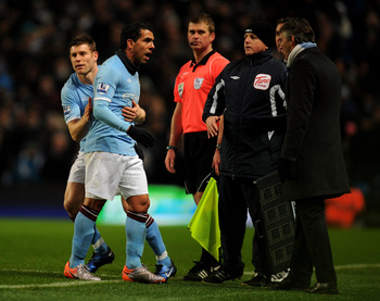 MANCHESTER, ENGLAND - DECEMBER 04:  Carlos Tevez of Manchester City has words with Manchester City Manager Roberto Mancini after being substituted for team mate James Milner during the Barclays Premier League match between Manchester City and Bolton Wande