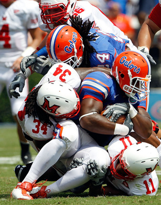 GAINESVILLE, FL - SEPTEMBER 04:  Linebacker Jonathan Bostic #52 of the Florida Gators is tackled by Thomas Merriweather #34 of the Miami University RedHawks following a interceptionat Ben Hill Griffin Stadium on September 4, 2010 in Gainesville, Florida.