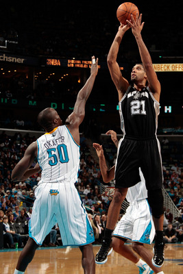 NEW ORLEANS - NOVEMBER 28:  Tim Duncan #21 of the San Antonio Spurs shoots the ball over Emeka Okafor #50 of the New Orleans Hornets at the New Orleans Arena on November 28, 2010 in New Orleans, Louisiana.  The Spurs defeated the Hornets 109-95.  NOTE TO