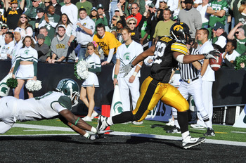 IOWA CITY, IA - OCTOBER 30: Running back Adam Robinson #32 of the University of Iowa Hawkeyes runs the ball into the end zone for a touchdown as line backer Greg Jones #53 of the Michigan State Spartans defends during the first half of play at Kinnick Sta