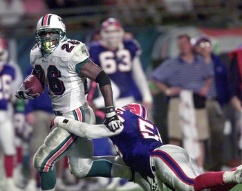 6 Jan 2002: Lamar Smith # 26 of the Miami Dolphins gets away from Jay Foreman # 55 of the Buffalo Bills in the fourth quarter at Pro Player Stadium in Miami Florida. Dolphins won 34-7. DIGITAL IMAGE. Mandatory Credit: Eliot Schechter/Getty Images