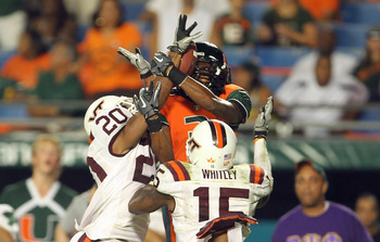 MIAMI - NOVEMBER 20: Travis Benjamin #3 of the Miami Hurricanes goes up for a catch before being interfered with by Eddie Whitley #15 and Jayron Hosley #20 of the Virginia Tech Hokies at Sun Life Stadium on November 20, 2010 in Miami, Florida.  (Photo by