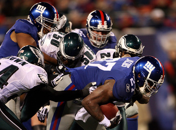 EAST RUTHERFORD, NJ - DECEMBER 13:  Brandon Jacobs #27 of the New York Giants runs the ball against Sheldon Brown #24 and Will Witherspoon #50 of the Philadelphia Eagles at Giants Stadium on December 13, 2009 in East Rutherford, New Jersey.  (Photo by Mic