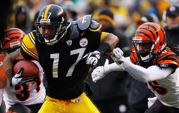 PITTSBURGH - DECEMBER 12:  Mike Wallace #17 of the Pittsburgh Steelers attempts to evade a tackle by Johnathan Wade #26 of the Cincinnati Bengals during the game on December 12, 2010 at Heinz Field in Pittsburgh, Pennsylvania.  (Photo by Jared Wickerham/G